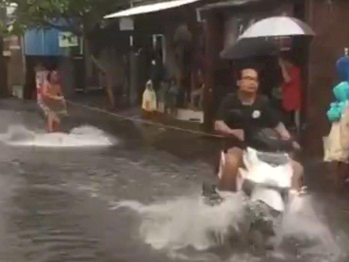Wih! Pria Ini Memanfaatkan Banjir Untuk Atraksi Surfing