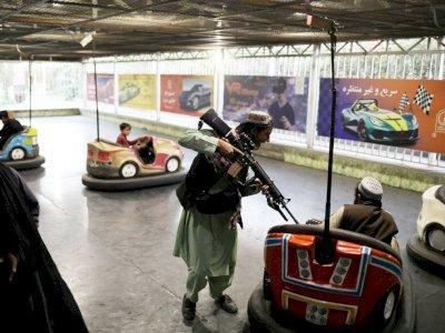 Sambil Tenteng Senjata, Milisi Taliban Asyik Bermain Bom-bom Car Bersama Anak-anak