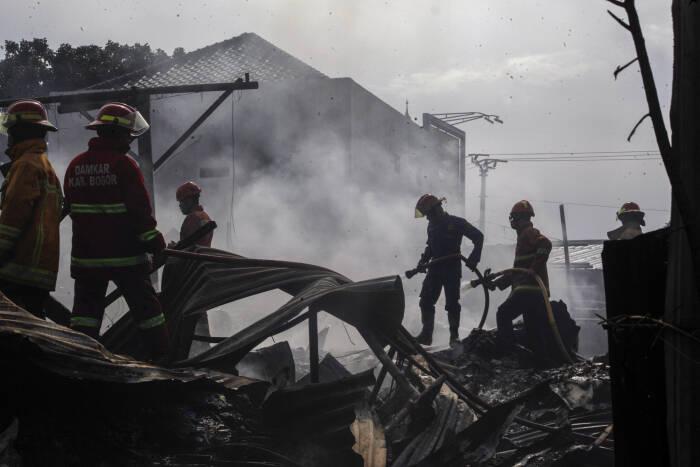 Petugas pemadam kebakaran memadamkan sisa kebakaran gudang barang bekas di Pondok Rajeg