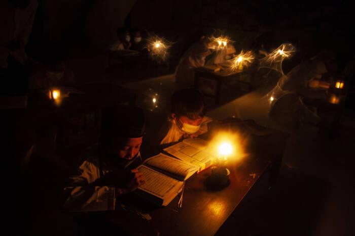 Sejumlah santri mengaji Al Quran menggunakan penerangan lilin dan lampu minyak di masjid Pondok Pesantren Baitul Mustofa