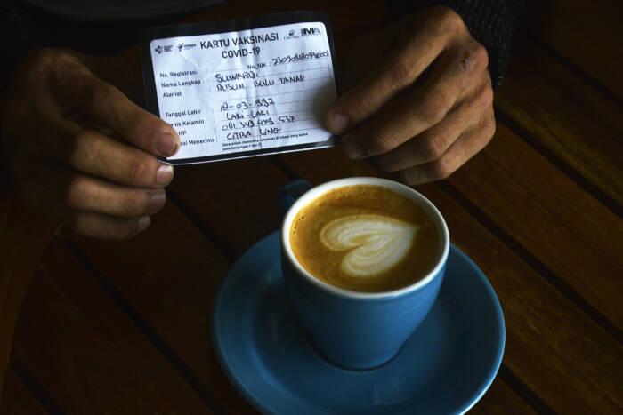 Warga yang sudah divaksin COVID-19 memperlihatkan kartu vaksin saat mendapatkan kopi gratis